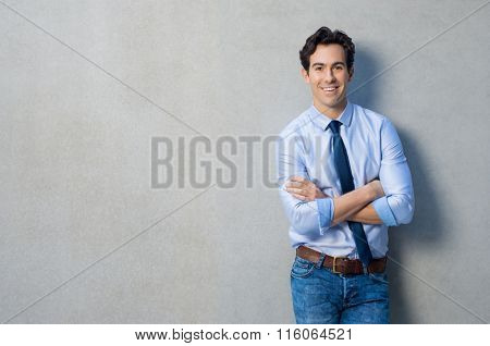 Happy smiling businessman leaning on a grey wall with copy space. Handsome young man leaning against a grey backgound. Portrait a satisfied man with arms crossed looking at camera and smiling.