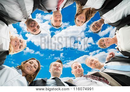 Diverse Business People Forming Huddle Against Sky