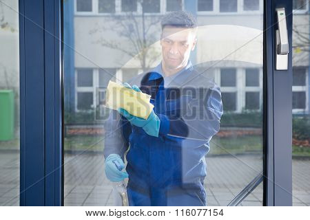 Happy Mature Male Worker Cleaning Glass With Rag