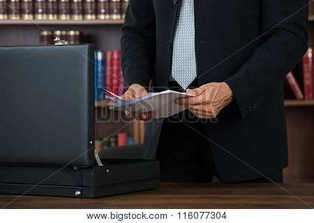 Lawyer Keeping Documents In Briefcase In Office