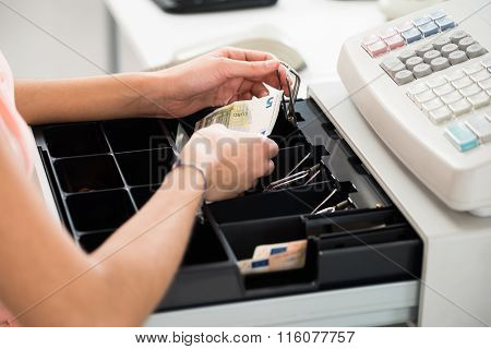Cashier Searching For Change In Cash Register Drawer