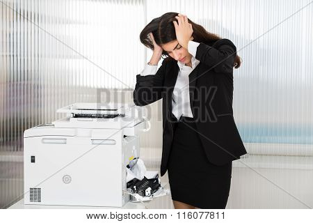 Irritated Businesswoman Looking At Paper Stuck In Printer