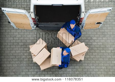 Delivery Men Carrying Cardboard Boxes Outside Truck