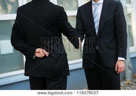 Dishonest Businessman Shaking Hands With Partner