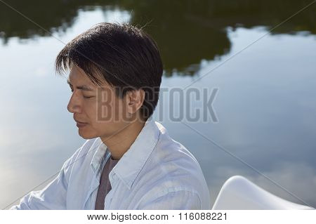 Man Meditating By Pond In Morning