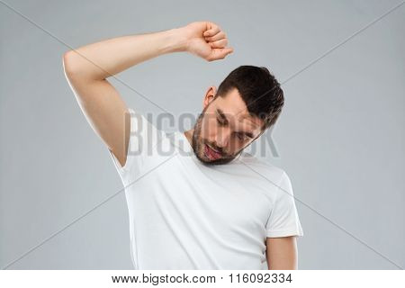 young making gallows gesture over gray background