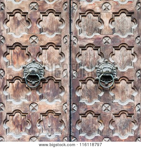 Detail Of A Wooden Door With Two Knocker Shaped A Lion's Head.