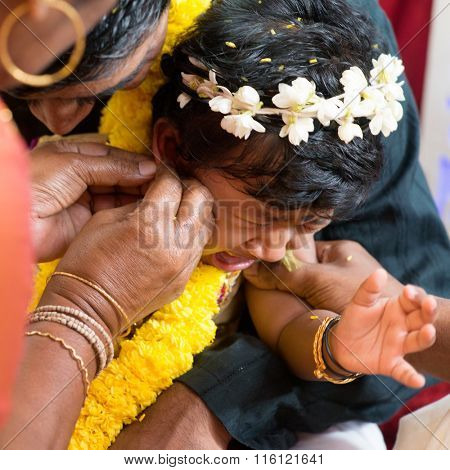 Baby girl crying during the karnavedha events. Traditional Indian Hindus ear piercing ceremony. India special rituals.