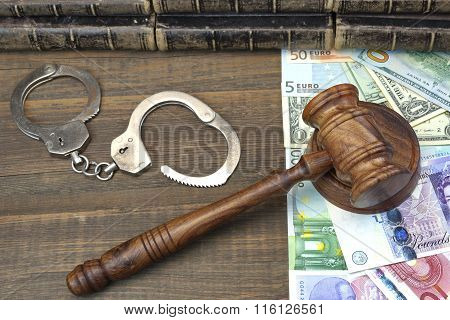 Judges Gavel, Handcuffs And International Money On Rough Wood Background.