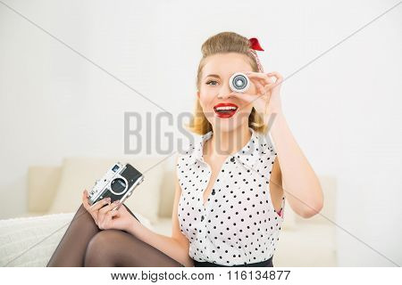 Young attractive girl playing with camera parts.