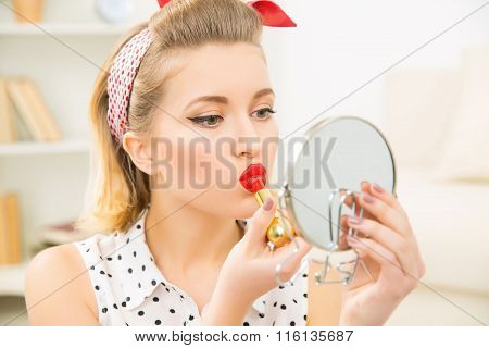 Young attractive girl busy with her make up.