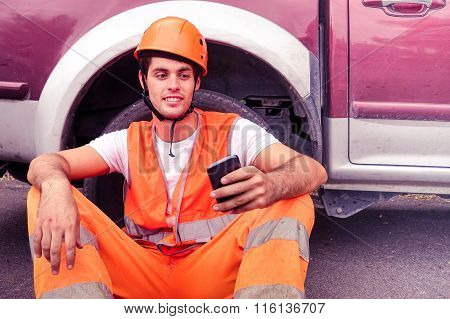 Worker With Mobile Phone And Helmet Relaxing Outdoors - Workman With Safety Clothes And Hardhat