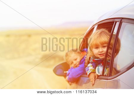 little girl and boy travel by car in mountains
