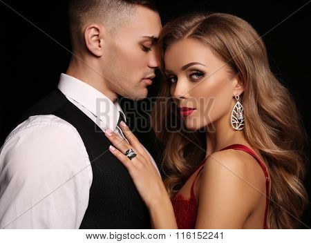 fashion studio photo of beautiful couple in elegant clothes gorgeous woman with long blond hair embracing handsome brunette man poster