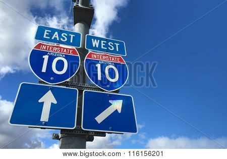 Arizona I10 East West Highway direction signs with copy space to right on blue sky