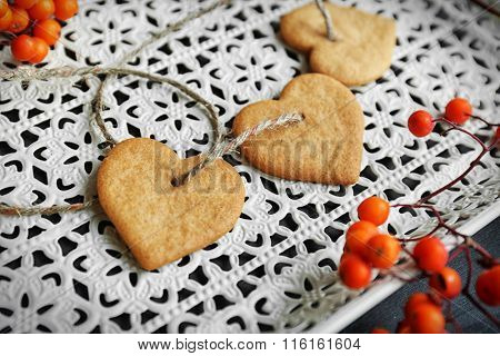 Heart shaped biscuits with ash berries and thread on a white tray