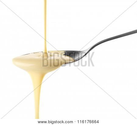 Condensed milk pouring from a spoon, isolated on white