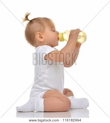 Infant Child Baby Toddler Sitting And Drinking Water From The Feeding Bottle