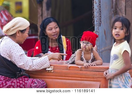 Little Girl With Glasses Presumably With Down Syndrome Is Enjoying Being With Her Sister, Mother And