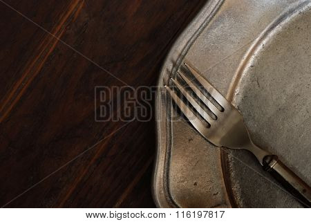 Vintage pewter fork and plate on dark rustic wood background with copy space.  Low key natural side-lighting for effect.