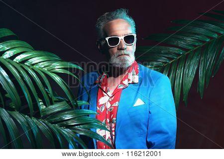 Stylish Senior Businessman Between Palm Leaves