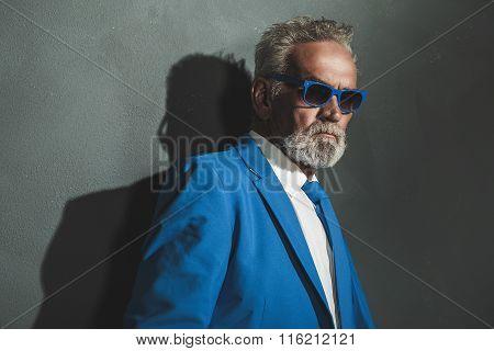 Senior Man In Blue Elegant Fashion Against Wall