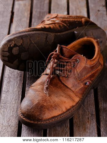 Old Worn Shoes On Grey Wooden Board