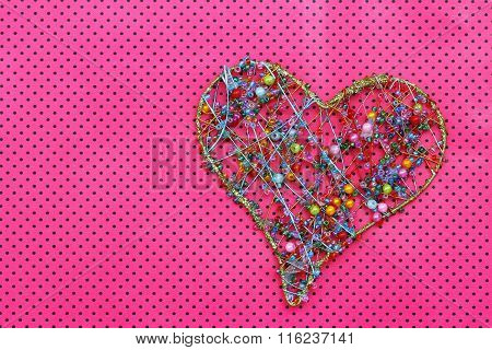 Heart made of colorful beads on pink dotty surface with copy space