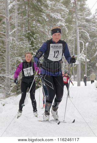 Smiling Cross Country Skiing Woman And Competitors In The Forest