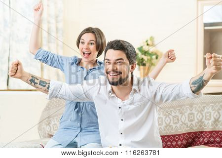 Happy couple feeling jubilant while watching TV