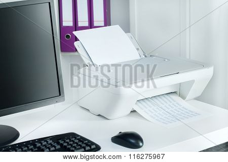 Composition of white printer and black computer in modern office