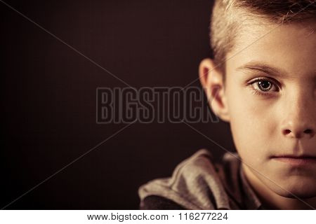 Half Face Of A Boy Against Brown With Copy Space