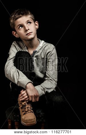 Pensive Young Boy Sitting Thinking