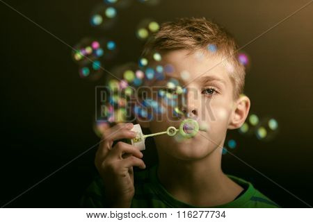 Young Boy Blowing Iridescent Bubbles