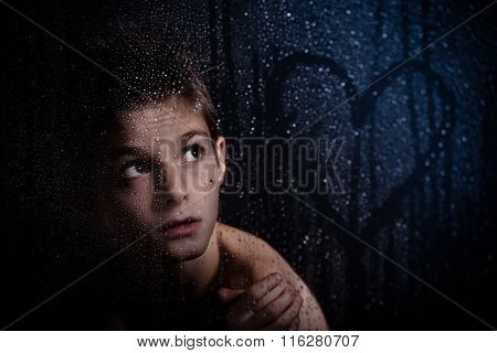 Young Boy Looking At Heart Shape On Misty Glass