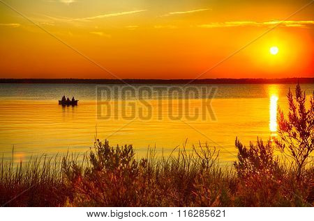 Kure Beach, NC - August 14 2015 - Fort Fisher Air Force Recreation Center Kure Beach North Carolina USA: A family views the sunset from a canoe on the Cape Fear River.