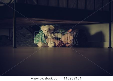 Scared Boy Sleeping Under His Bed With Teddy Bear