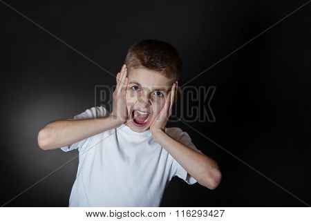 Angry Boy Shouting With Hands Holding On His Face