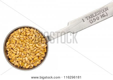 golden flax seed seed on metal measuring tablespoon, isolated on white
