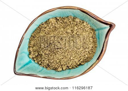 hemp seed  protein powder on an isolated leaf shaped ceramic bowl, top view