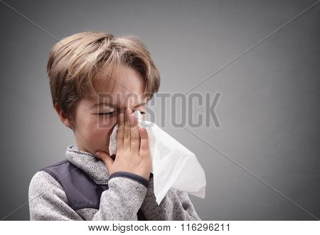Boy suffering flu or a cold blowing his nose with a tissue