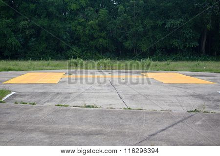 yellow sign on concrete Helipad with forest background