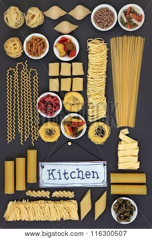 Large dried italian pasta food sampler with old metal kitchen sign on grey background.