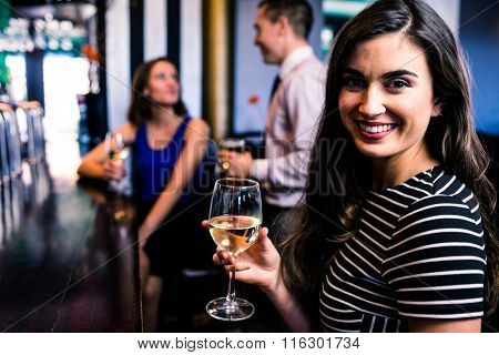 Portrait of woman having a drink with friends in a bar