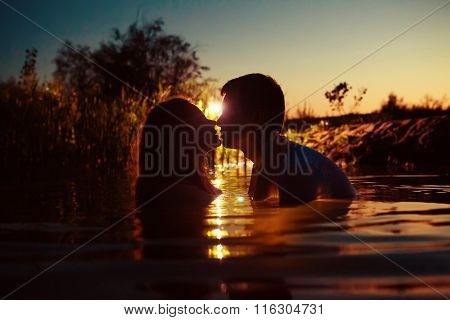 Young Couple Is Kissing In The River On The Summer Sunset Background.