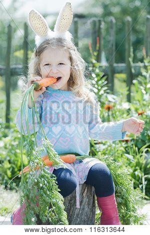 Preschooler blonde girl wearing Easter rabbit costume gnawing fresh carrot