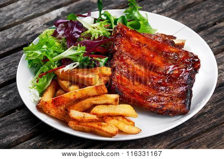 Roasted Pork Rib,  Fried Potato on white plate with Vegetables.