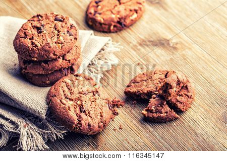 Chocolate biscuit cookies. Chocolate cookies on white linen napkin on wooden table. poster