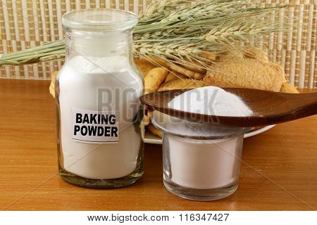 baking powder closeup in a glass jar and wooden spoon with cookie and wheat