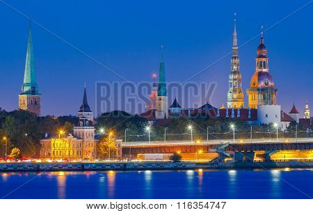 Evening view on the embankment of the Daugava River and the spiers of churches in Riga. poster